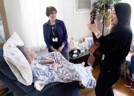 Woman singing and playing guitar for patient.